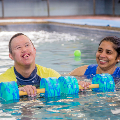 smiling male participant in pool with support worker