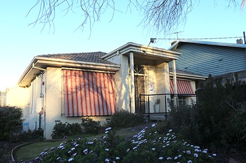 Front of white rendered house with ramp leading to front door and sun shades pulled over windows