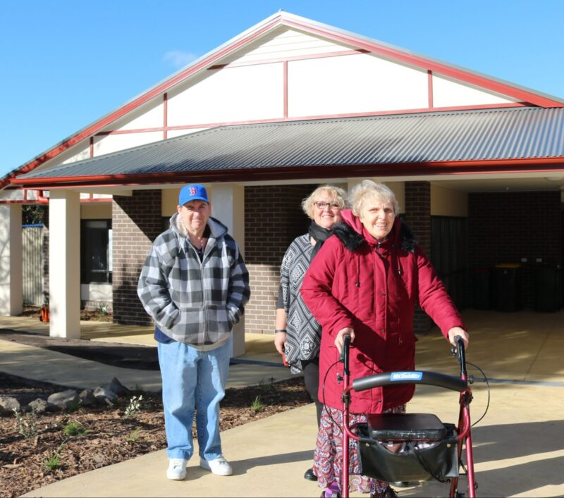 2 participants standing out the front of their supported independent living accomodation with support worker