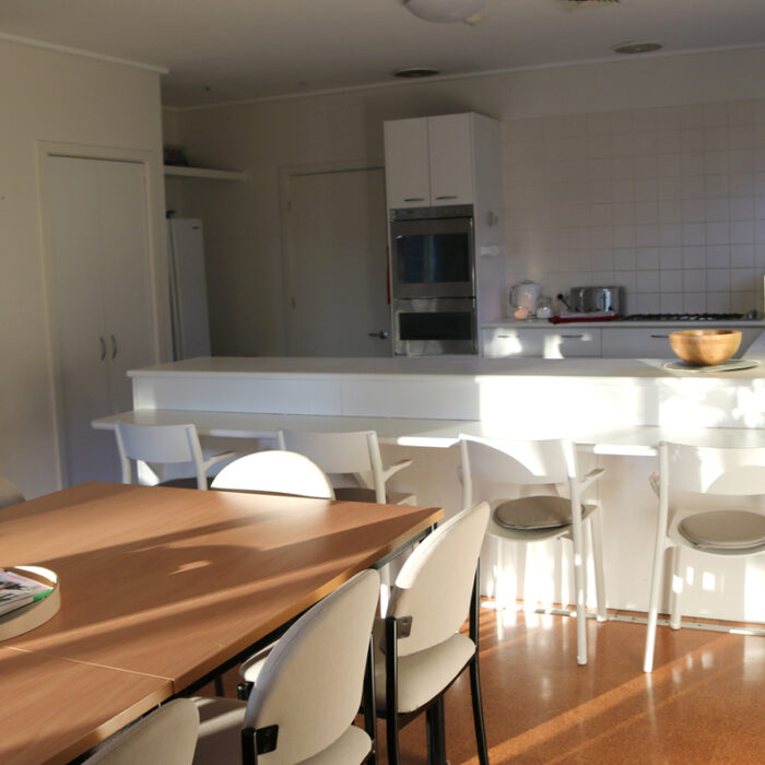 Tootgarook Holiday house kitchen area with breakfast bar with 4 stools and dining table