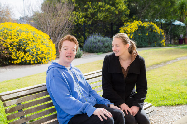 Young male participant Ben sitting on a park bench smiling with support worker next to his side