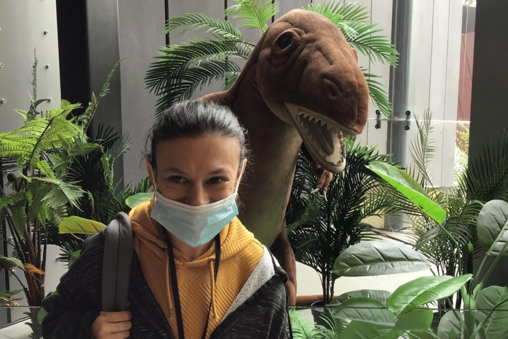 Young women on OC Connections day support activity with toy dinosaur behind her at the Melbourne Museum