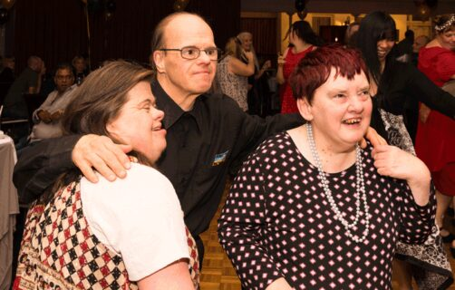 3 participants embracing at OC Connections night disco