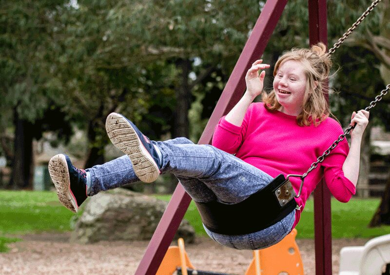 Young women swinging on a park swing smiling at OC Connections Day Support Fitness Activity