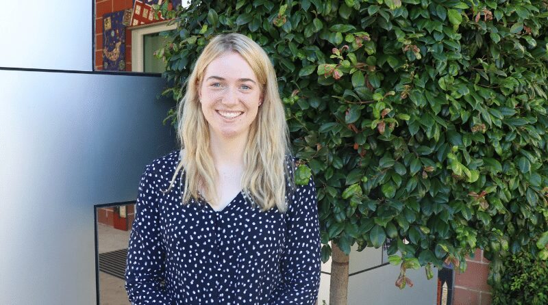 A photo of our Volunteer Coordinator, Alana. She has long blonde hair and is standing out the front of the OCC building